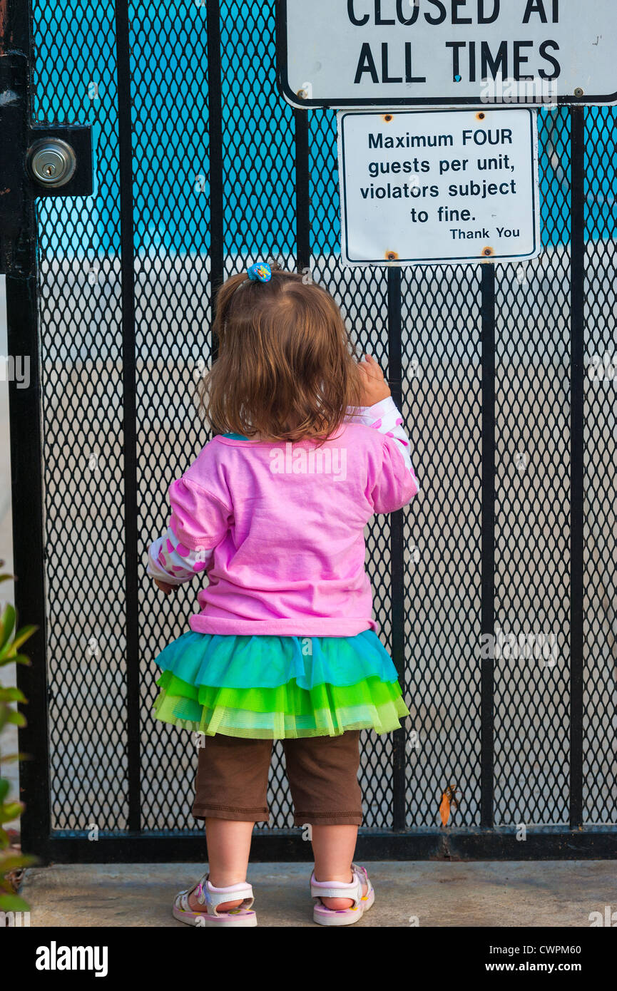 A Toddler Is Facing A Closed Gate To A Swimming Pool Safety Measure