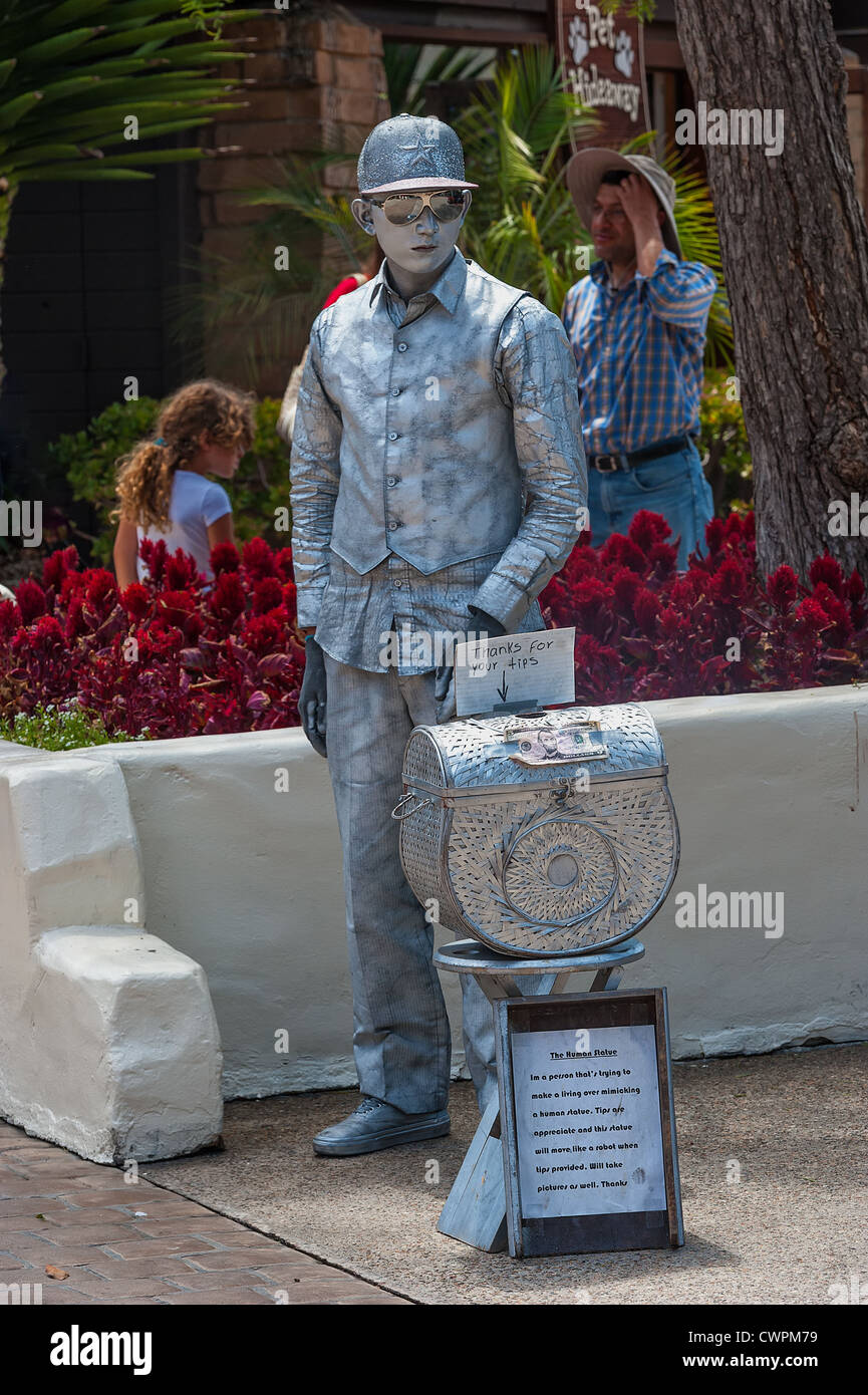 A mime performs at San Diego's Embarcadero Del Mar. Covered with silver body paint and imitating a robot. - Stock Image