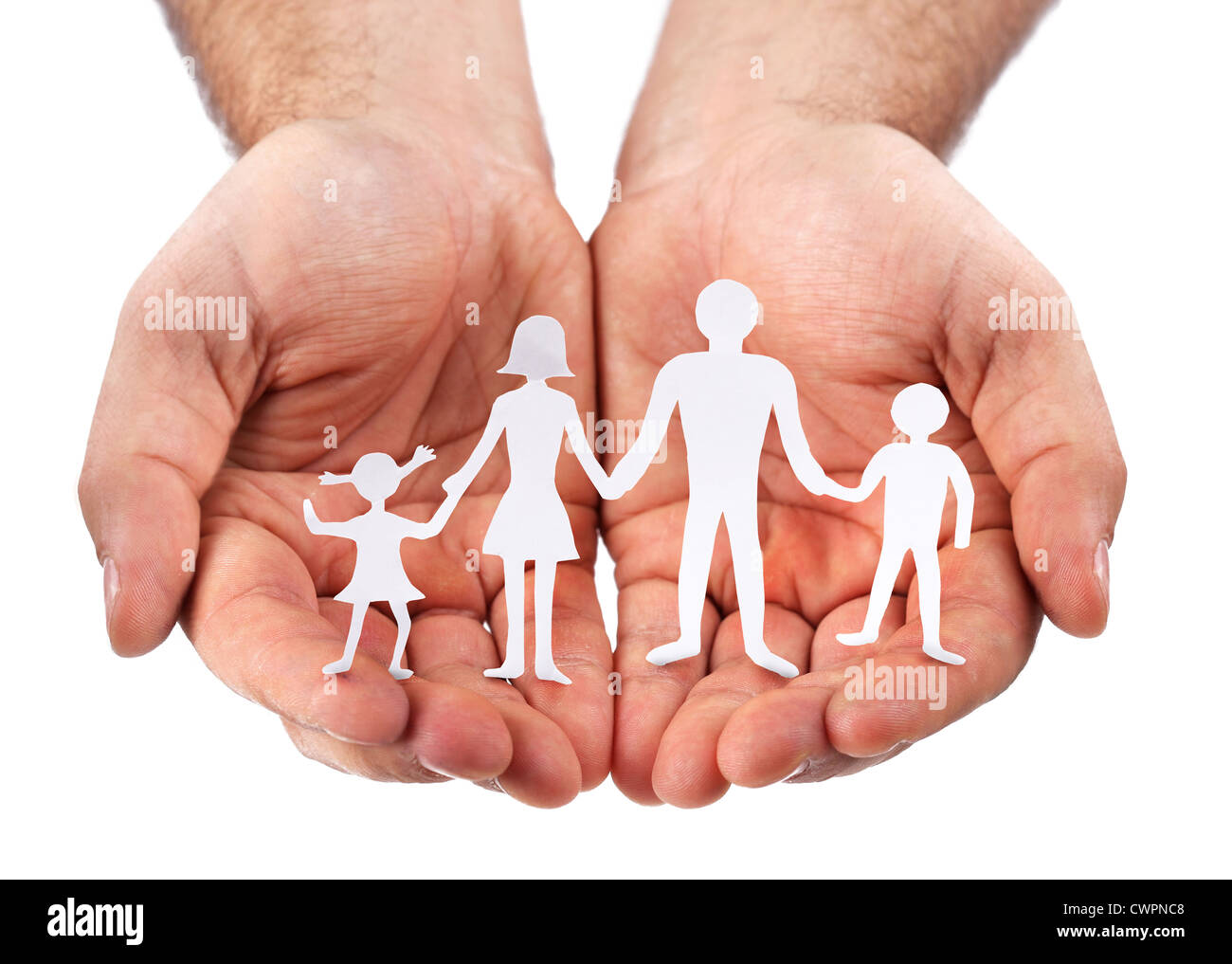 Cardboard figures of the family on a white background. The symbol of unity and happiness. Hands gently hug the family. - Stock Image