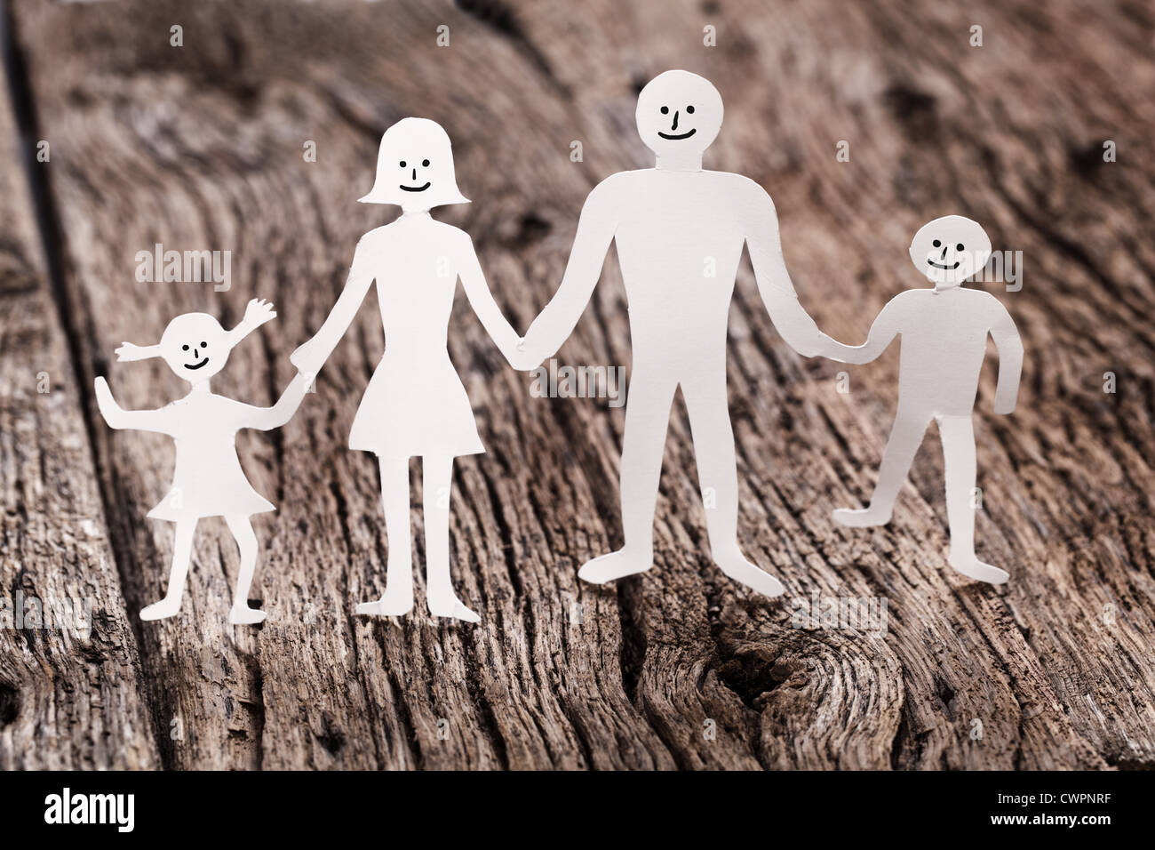 Cardboard figures of the family on a wooden table. The symbol of unity and happiness. Stock Photo