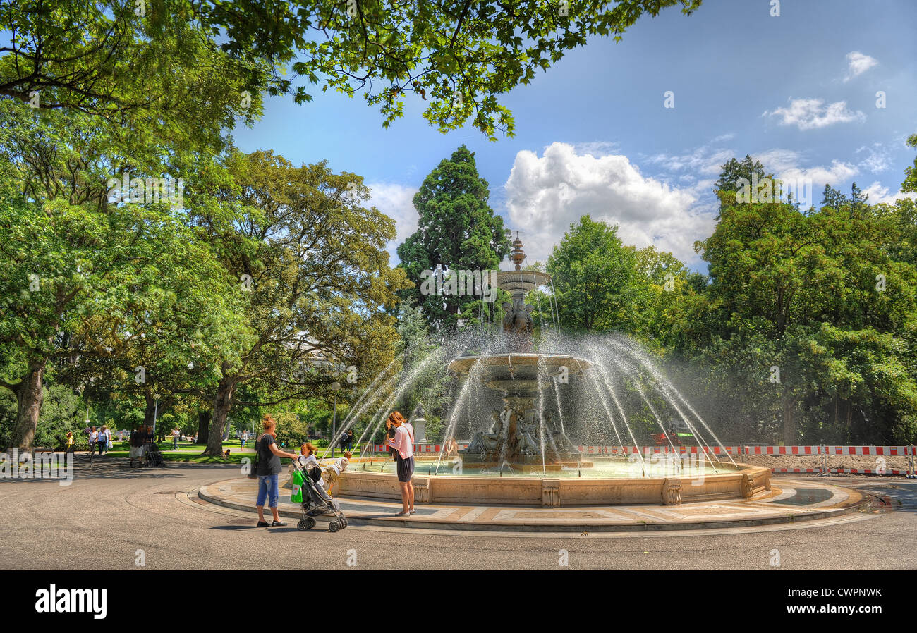 Women and children by a fountain in the English Gardens in Geneva, Switzerland on a summers days - Stock Image