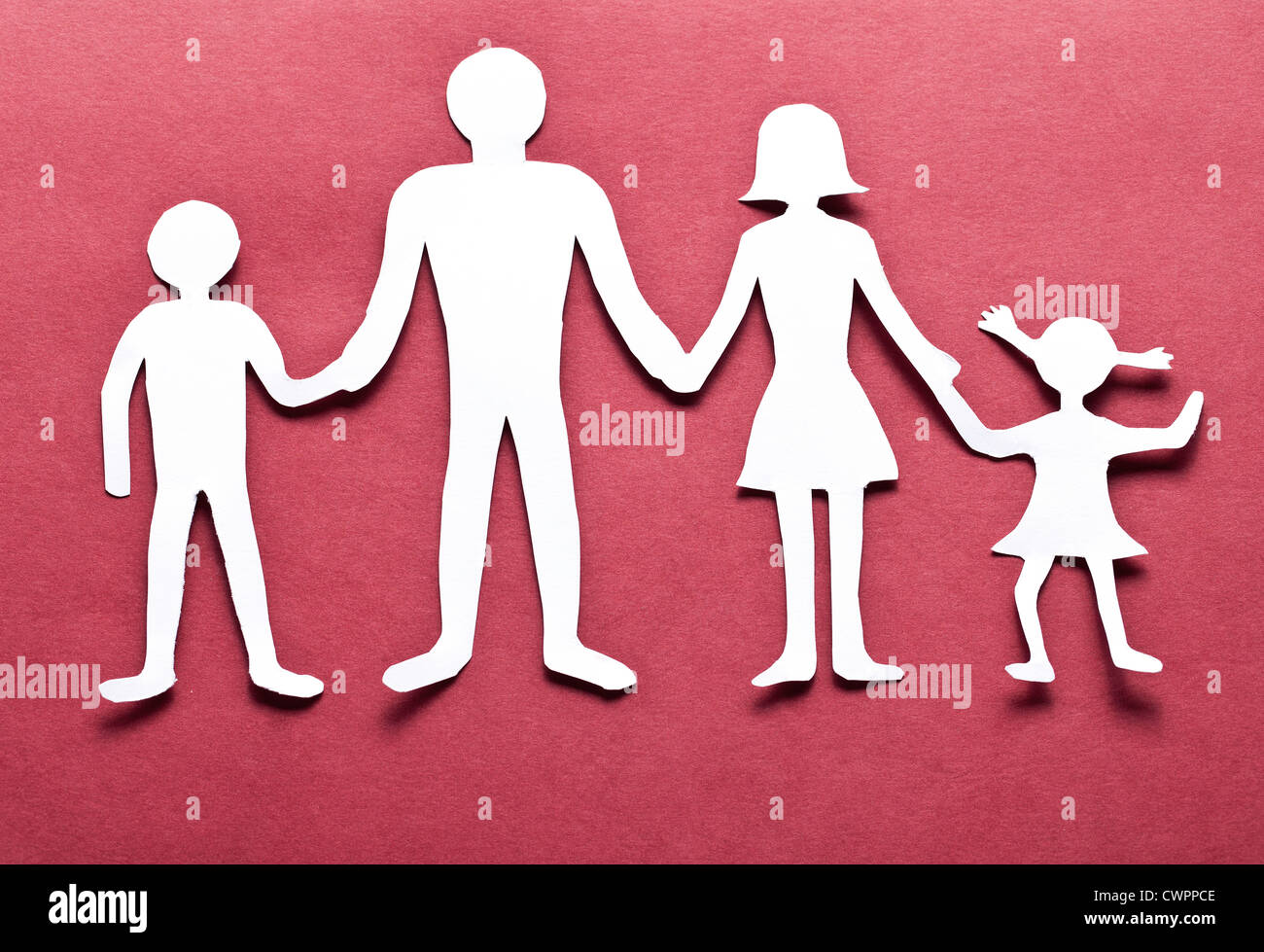 Cardboard figures of the family on a red background. The symbol of unity and happiness. - Stock Image