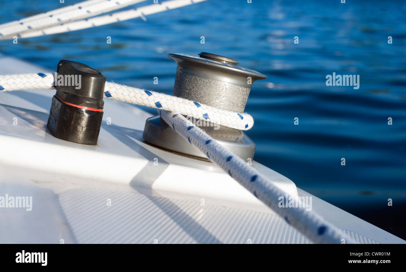 Winch, sheet, and clamp of a small dinghy in the evening light Stock Photo