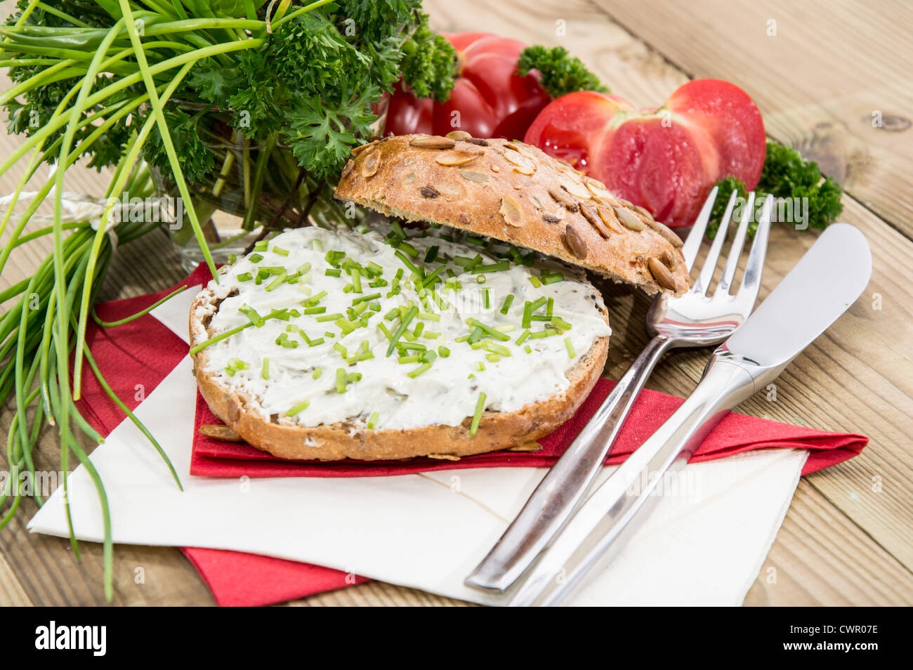 Fresh Creme Cheese on a roll topped with Chives - Stock Image