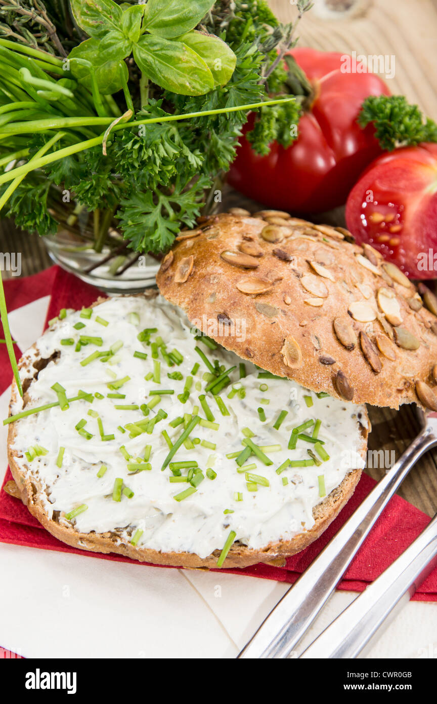 Roll with Cream Cheese and fresh Chives against wooden background - Stock Image