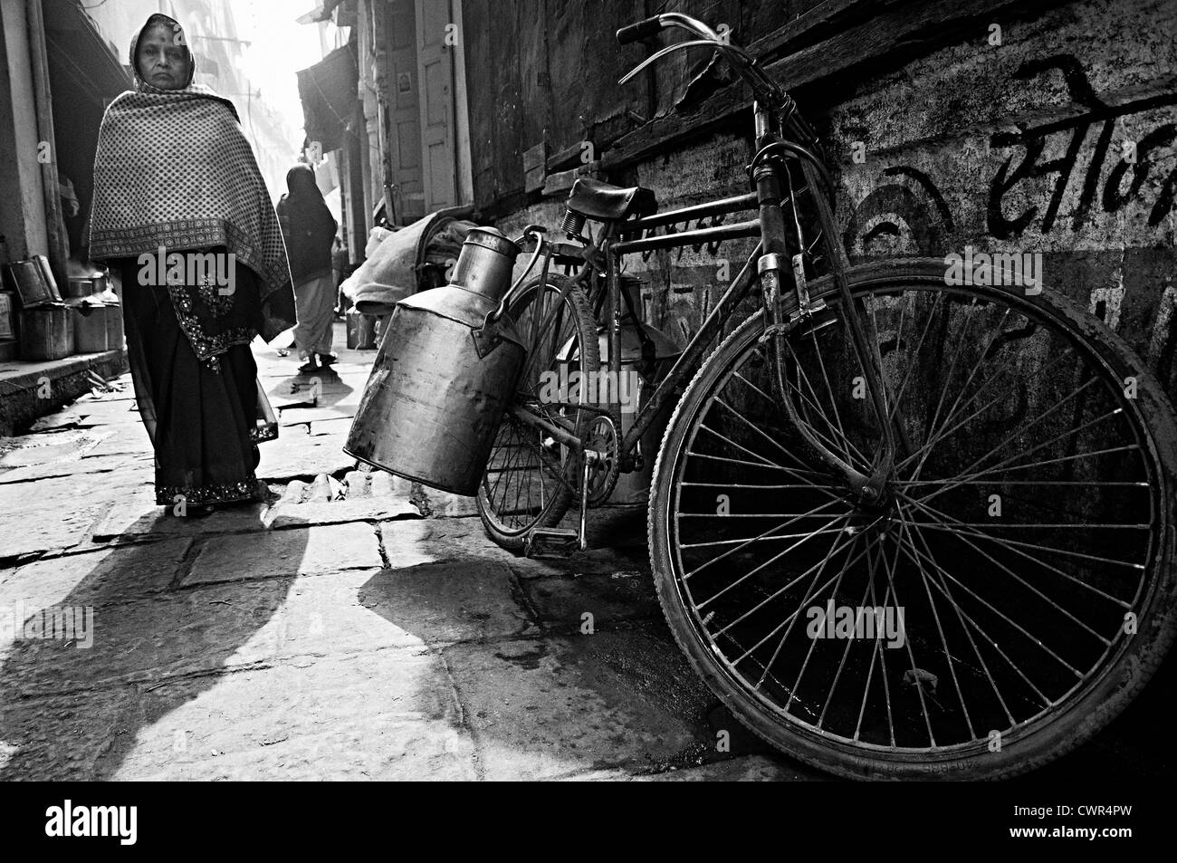 Milkman´s bicycle parked in an alley and woman coming. Varanasi,Uttar Pradesh, India - Stock Image