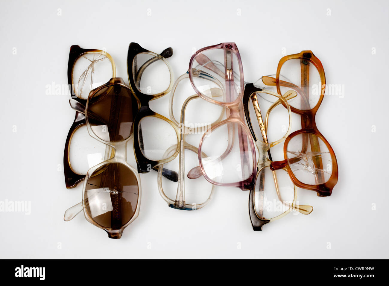 Many old horn-rimmed glasses with cracked lenses Stock Photo
