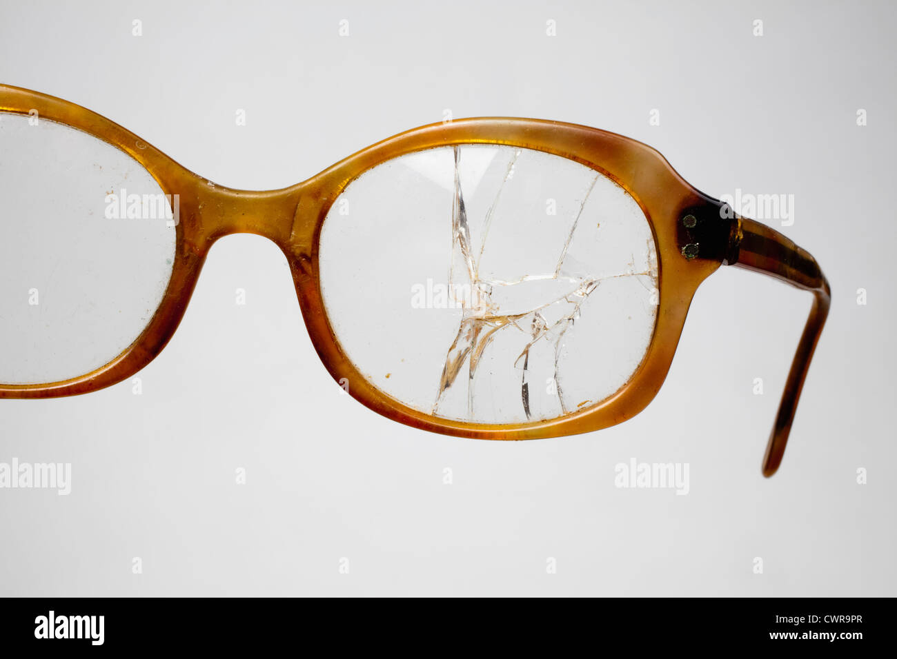 An old horn-rimmed glasses with a cracked lens - Stock Image