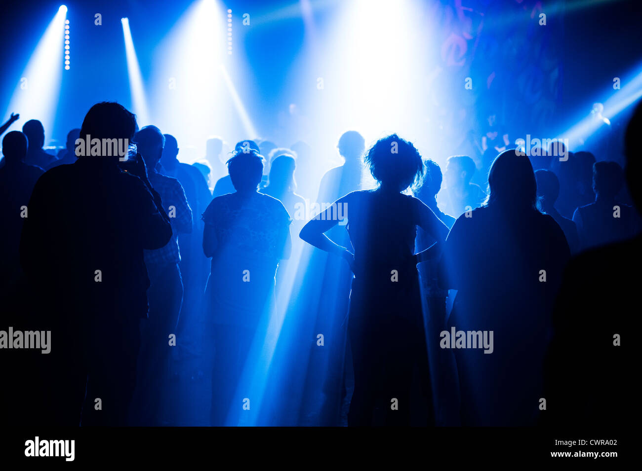 Young people silhouetted at concert gig music event nightclub club clubbers clubbing UK - Stock Image