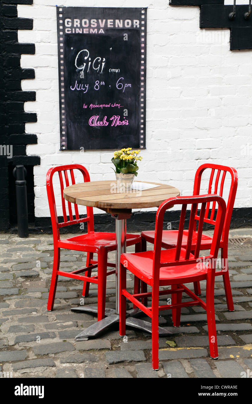 3 red chairs around a table with flowers outside the Grosvenor Cinema on Ashton Lane in the West End of Glasgow, - Stock Image