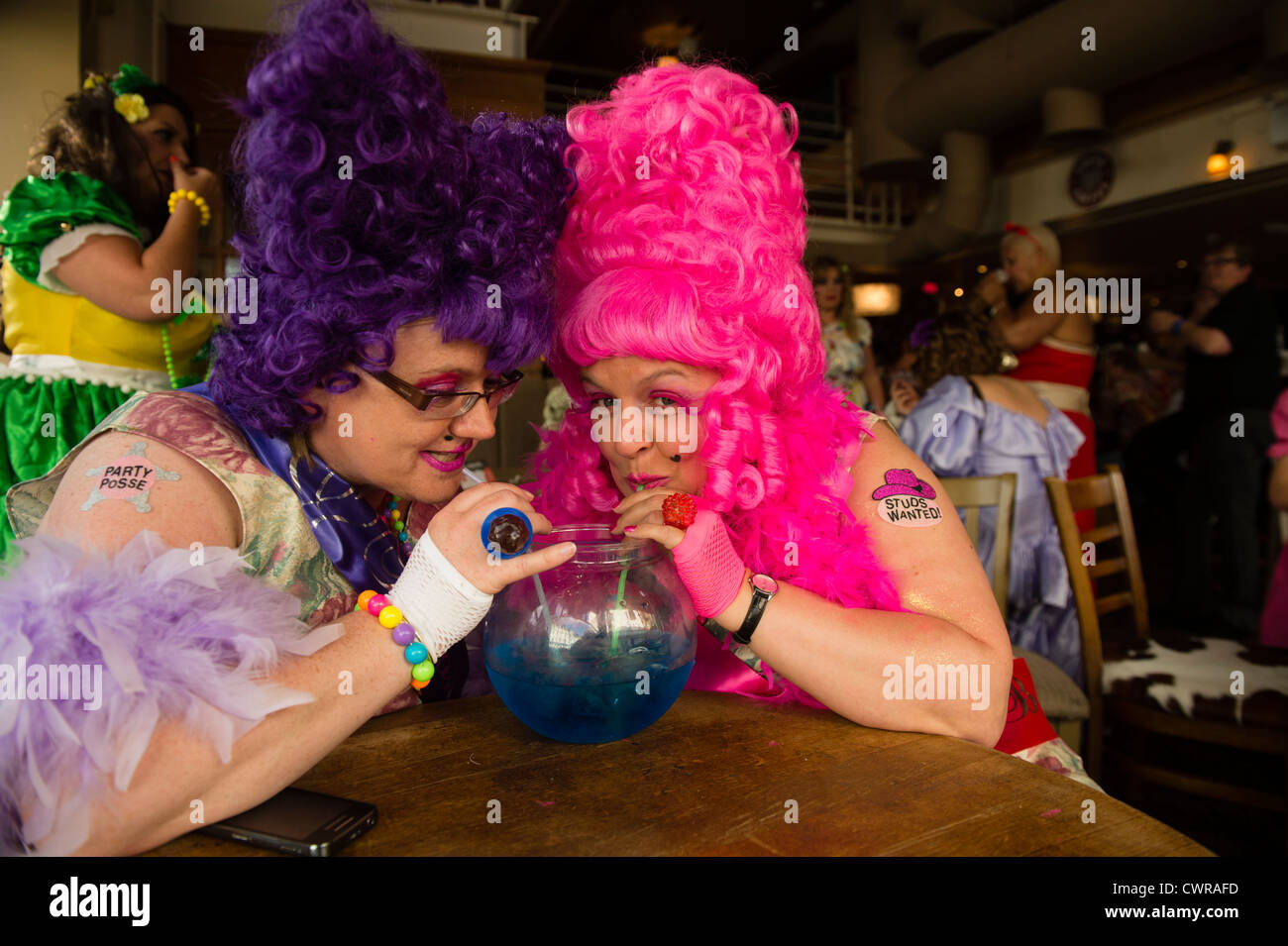 Women on a fancy dress bad taste ball gowns themed hen night party pub crawl, Aberystwyth Wales UK - Stock Image