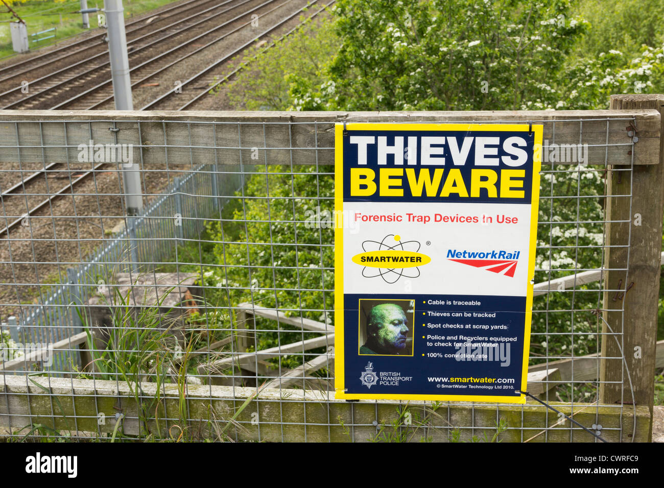 Smartwater in use warning signs near the West Coast mail line electrified railway as a deterrent to scrap metal - Stock Image