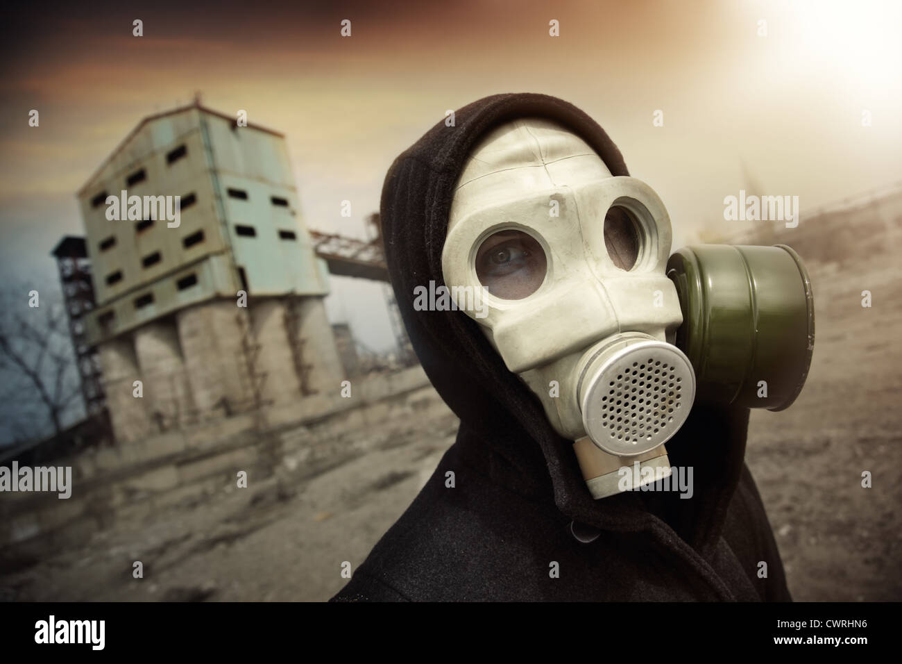 Man in protective gas mask near the industrial plant during radioactive sunset. Artistic colors and grain added - Stock Image