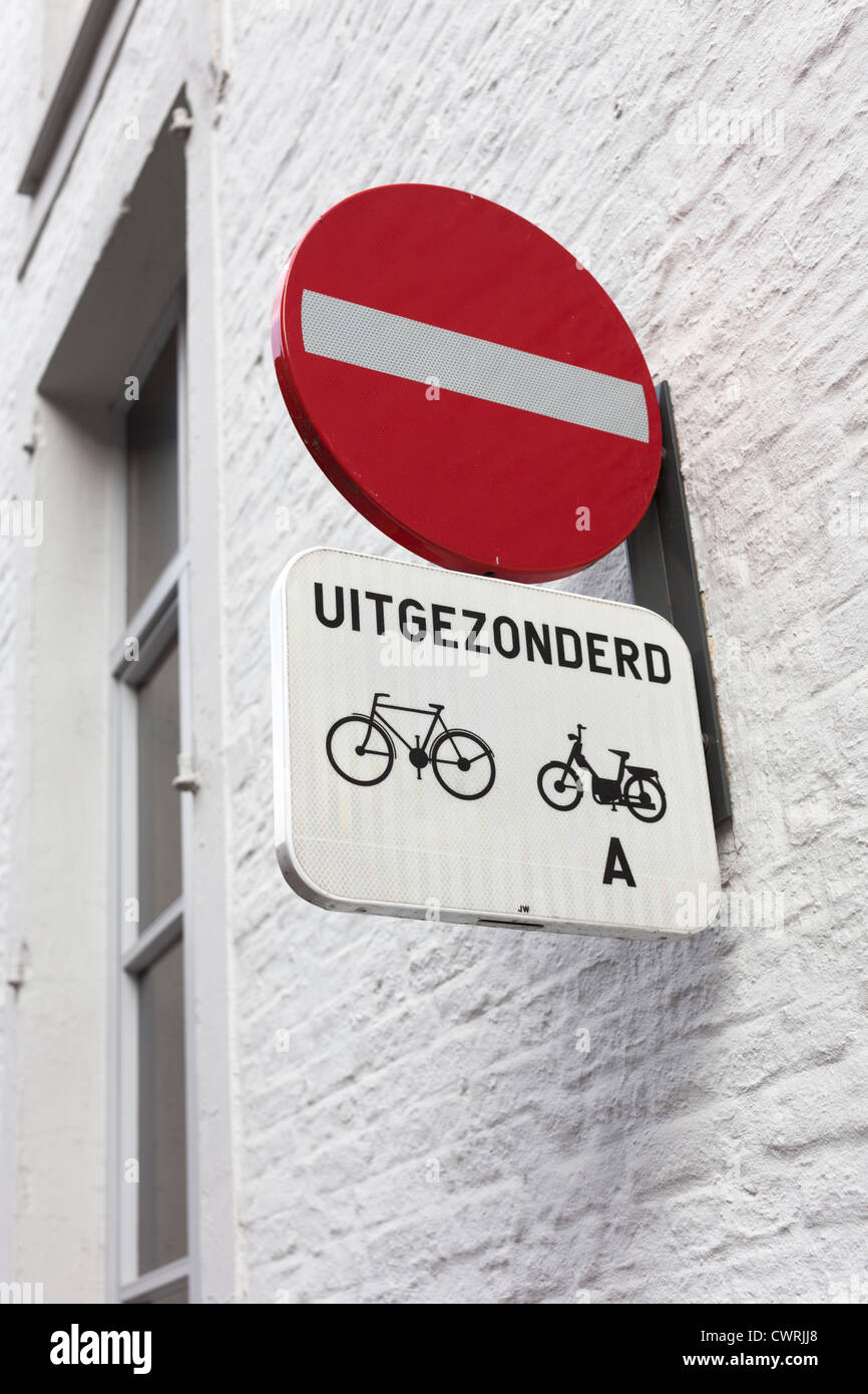 No entry sign in Bruges, Belgium, with Dutch word for 'except' [bicycles and mopeds] - Stock Image