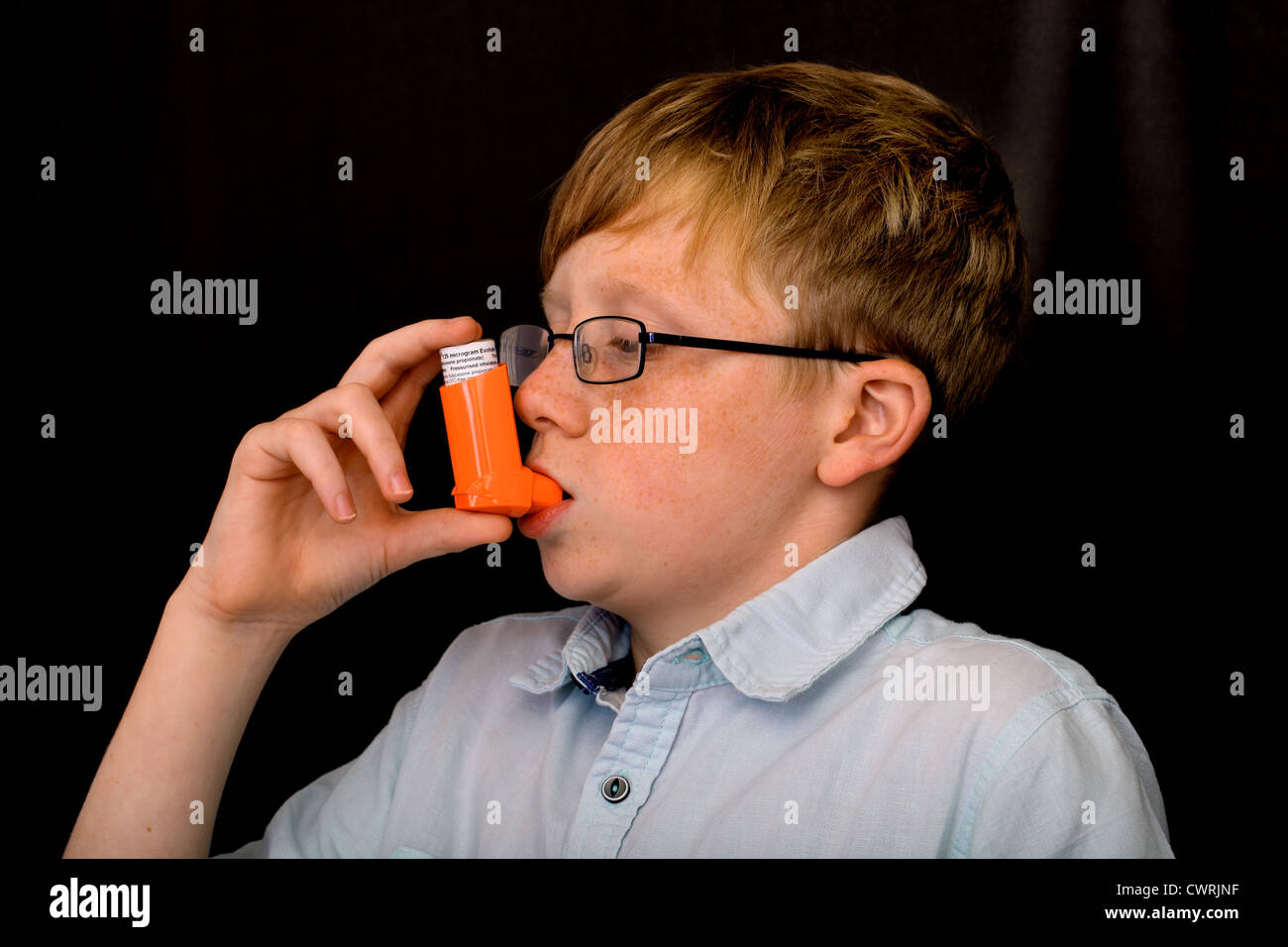A thirteen year old boy using an asthma pump - Stock Image