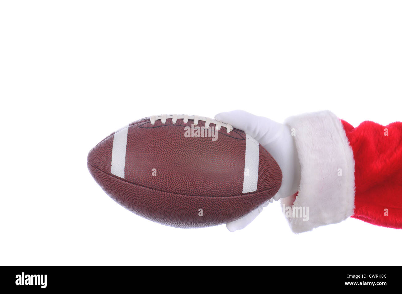 Santa Claus outstretched arm with an american football ready to hand off. Horizontal format over a white background. - Stock Image
