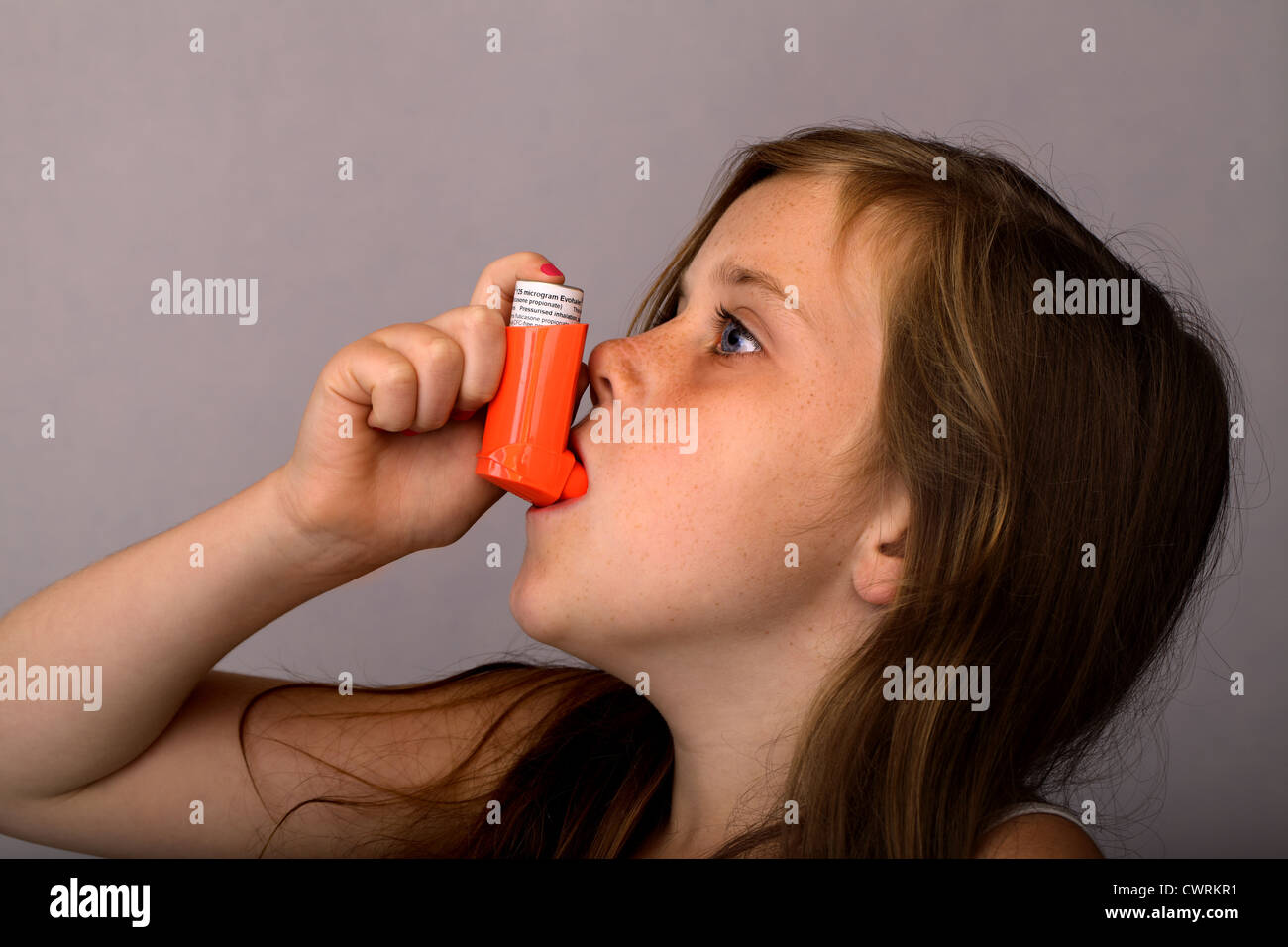 A 10 year old girl using an asthma pump - Stock Image