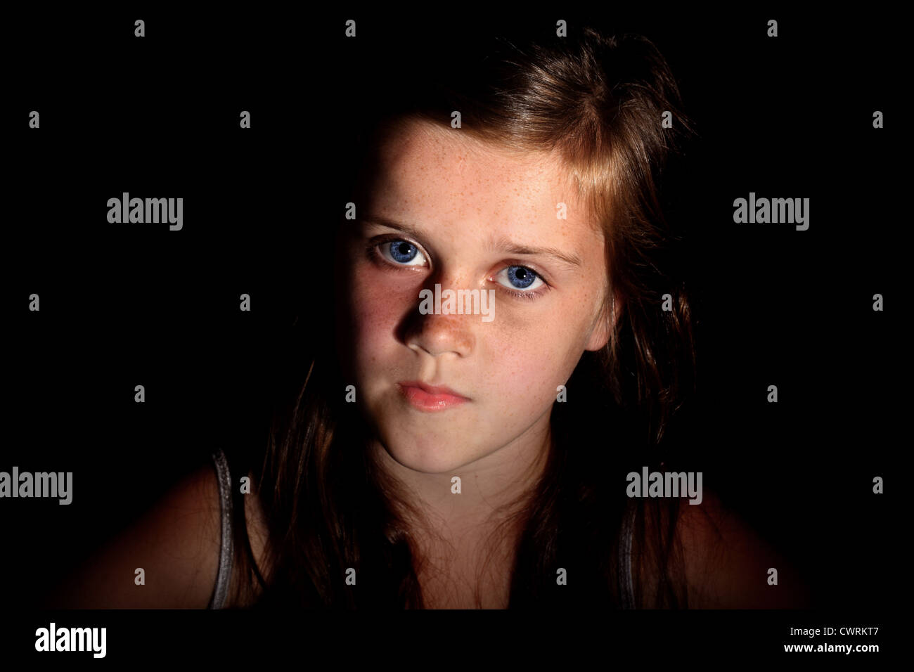 A sidelit image of a 10 year old girl looking at the viewer - Stock Image