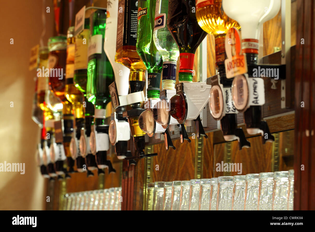 Bottles of spirits with optics on display at a British bar - Stock Image