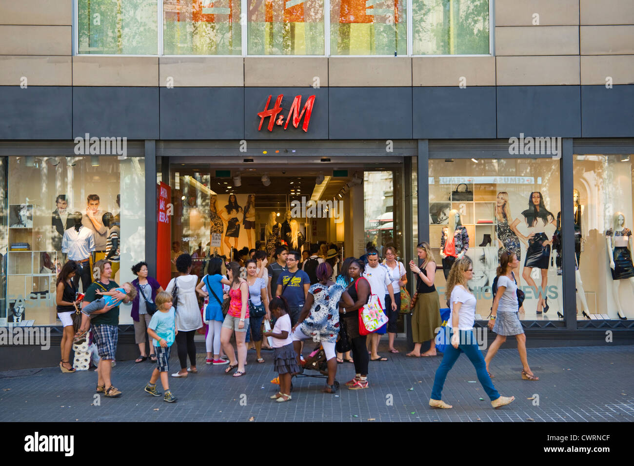 Barcelona people shopping. Exterior of H&M store with people shopping in Barcelona, Catalonia, Spain, ES - Stock Image