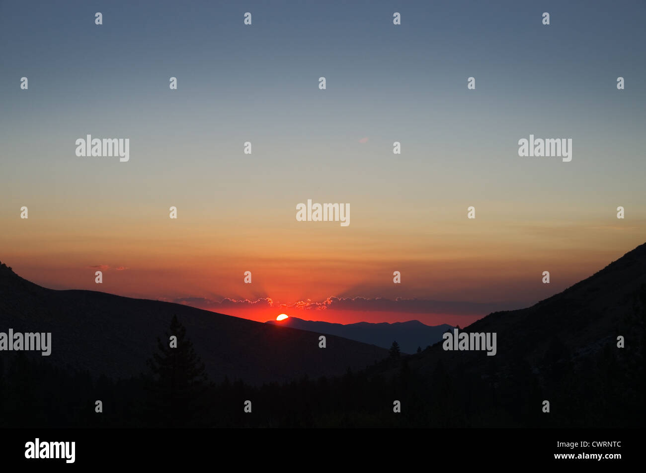 mountain sunrise with brightly edged clouds and copy space - Stock Image