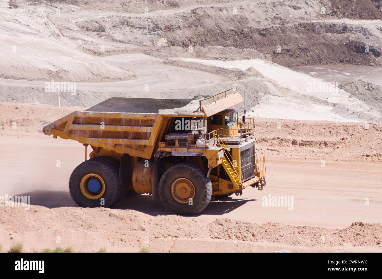 large yellow haul or dump truck driving at an open pit mine