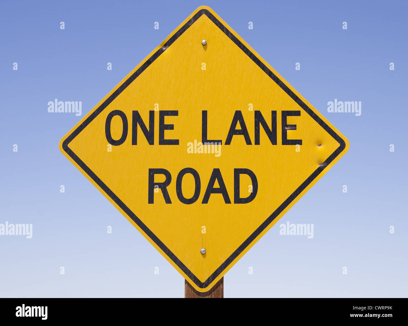 yellow and black one lane road sign with blue sky background - Stock Image
