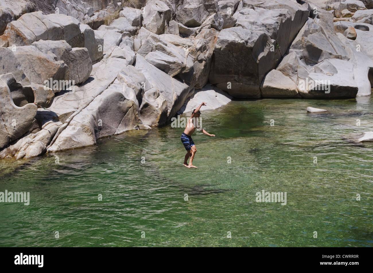a man slacklining over the Yuba River - Stock Image