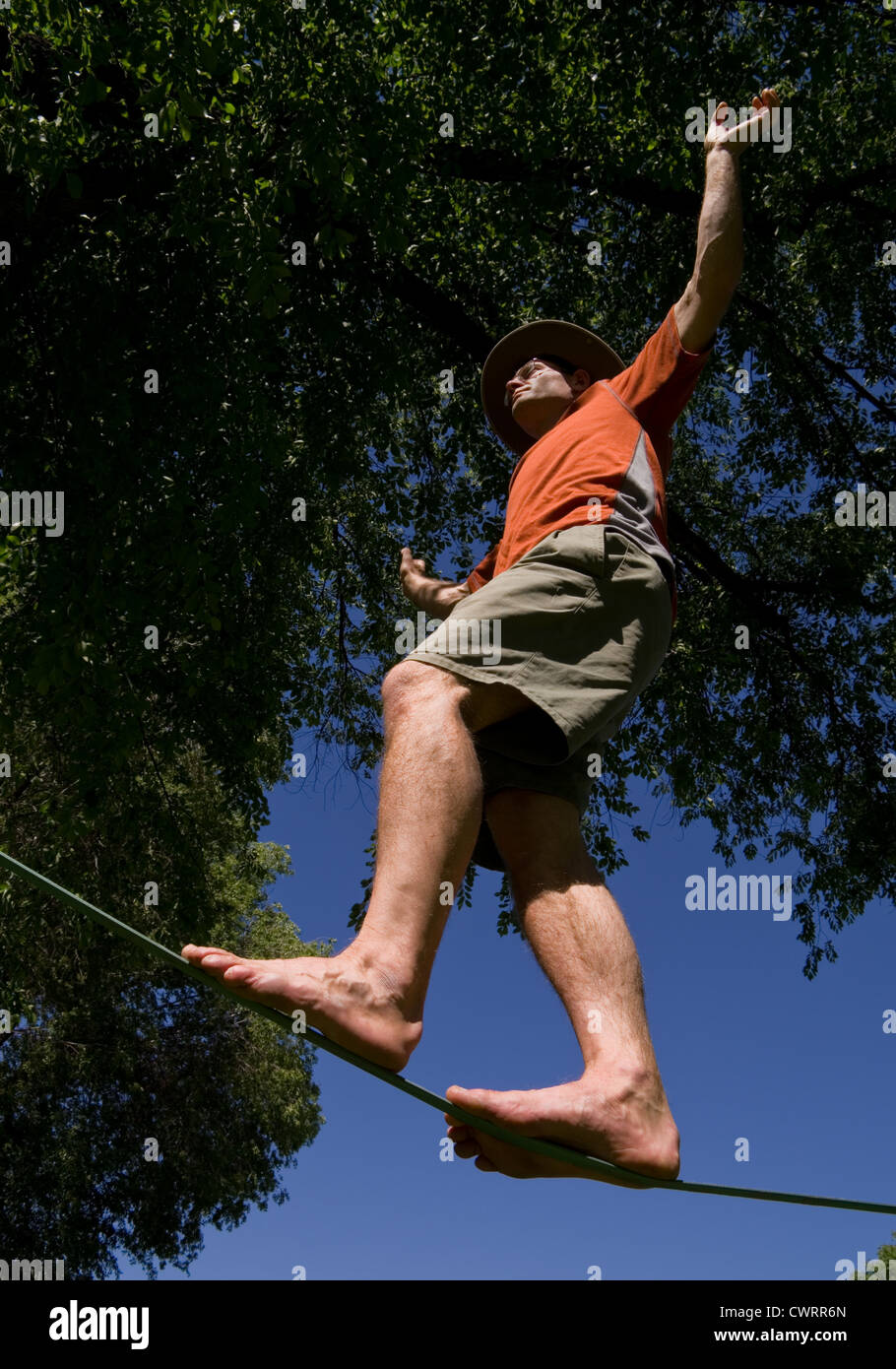 man balancing on a slackline pictured from below - Stock Image