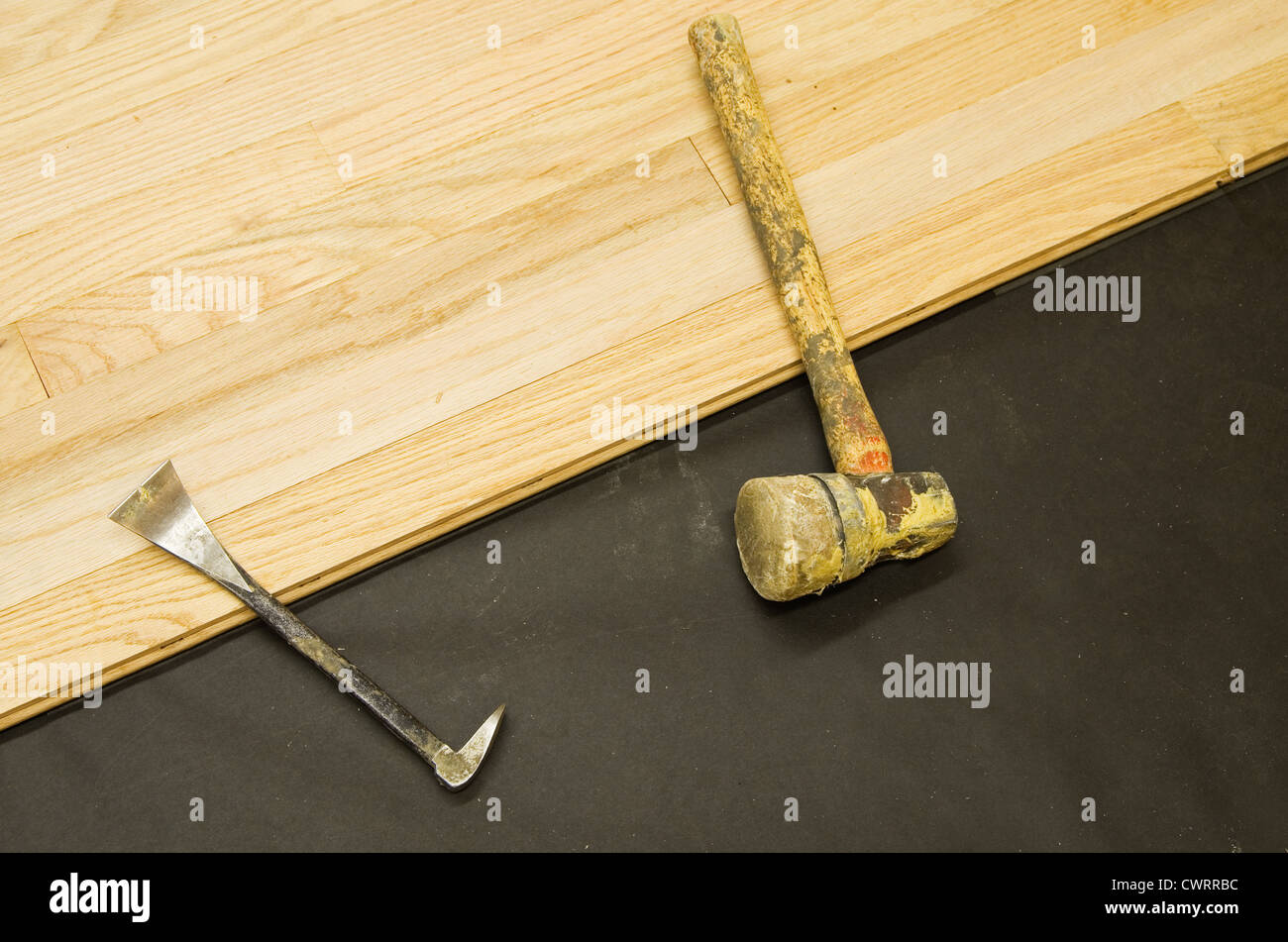 installation of hardwood flooring with prybar and mallet tools - Stock Image