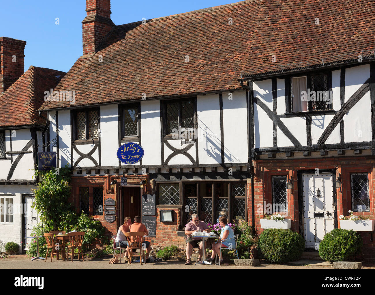 People dining outside Shelly's tea rooms serving cream teas in picturesque old Kentish village on the Pilgrims Way. Stock Photo