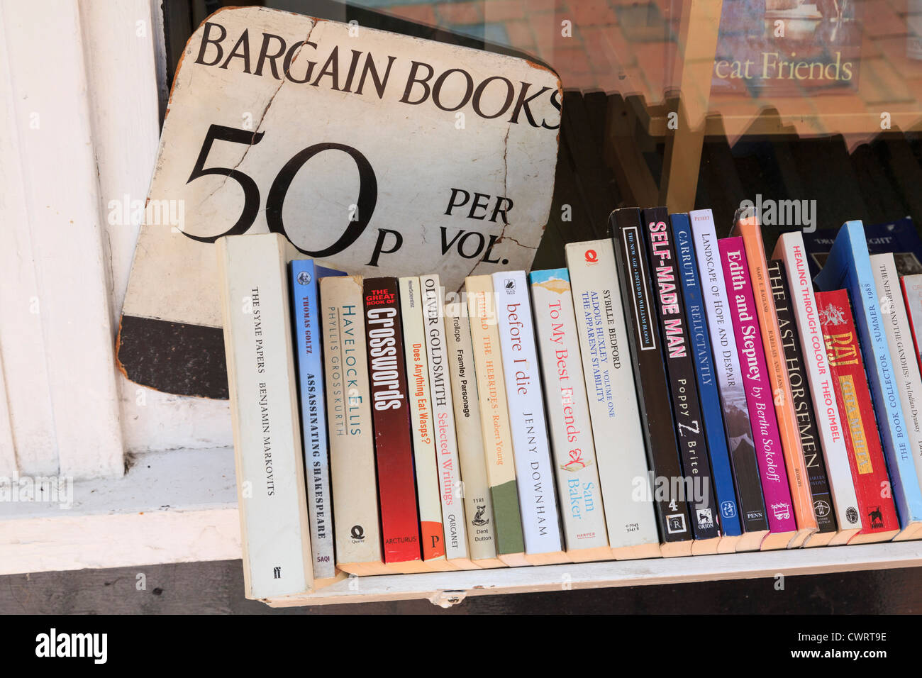 Sign for old bargain paperback books on sale on a shelf for 50p per volume outside a bookshop in England UK Britain - Stock Image
