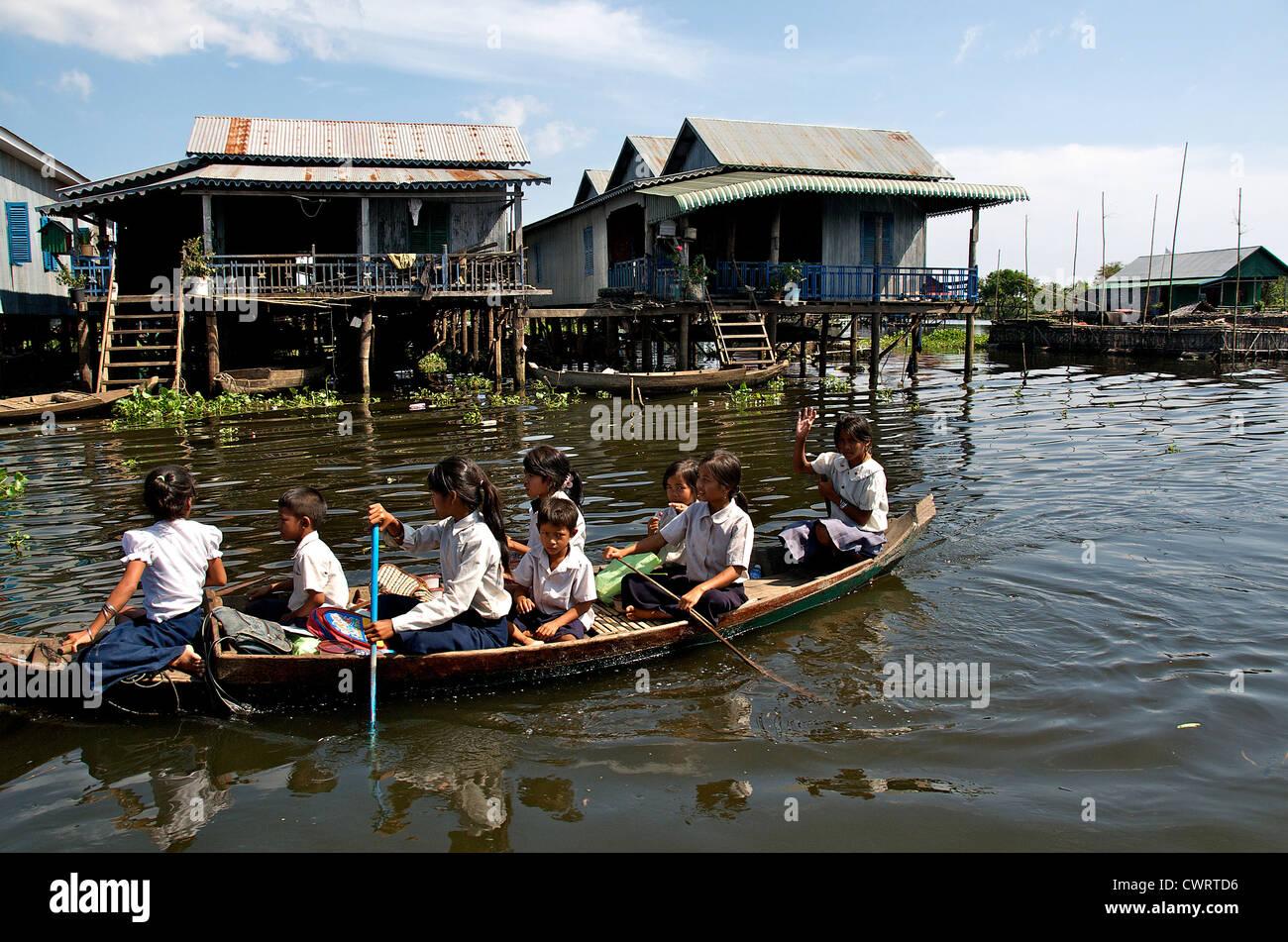 schoolchildren boat boating row rowing water Tonle Sap lake - Stock Image
