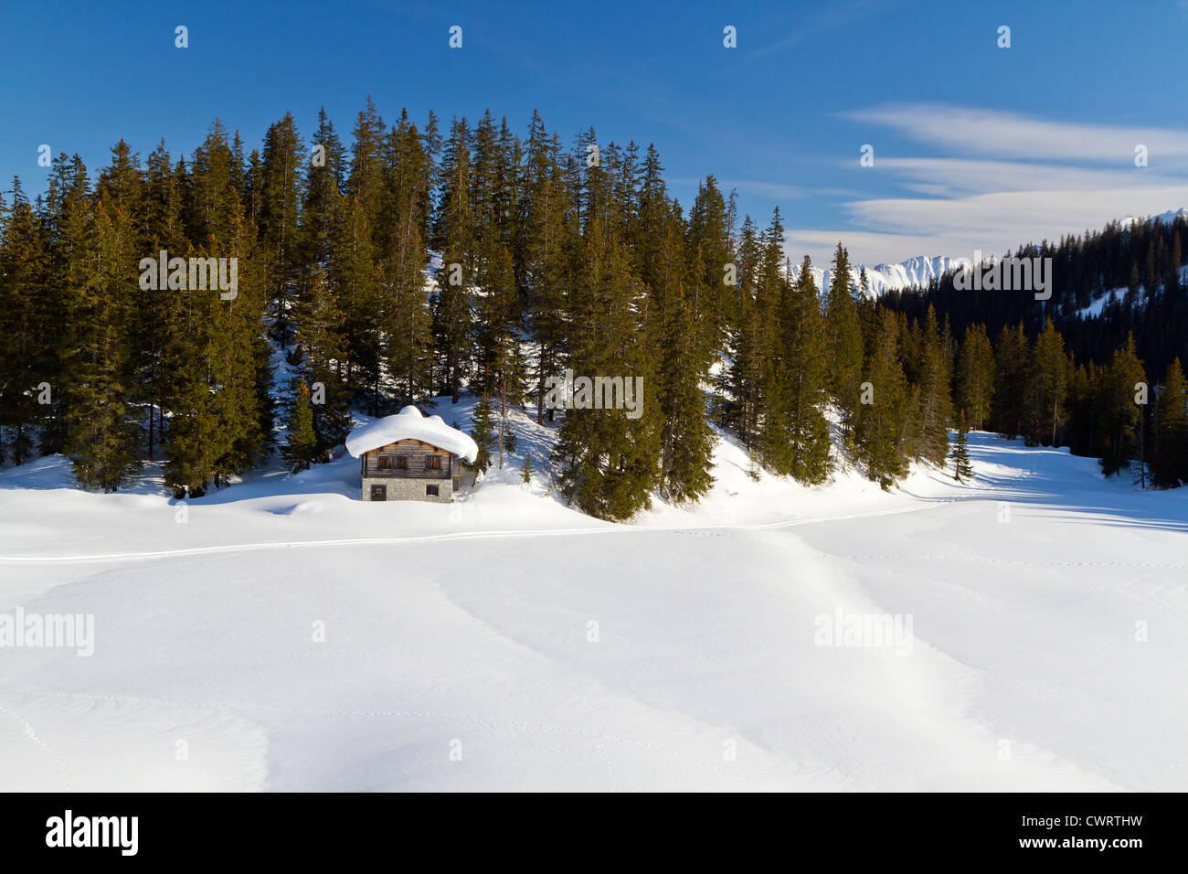 Log cabin in snow in the Alps - Stock Image