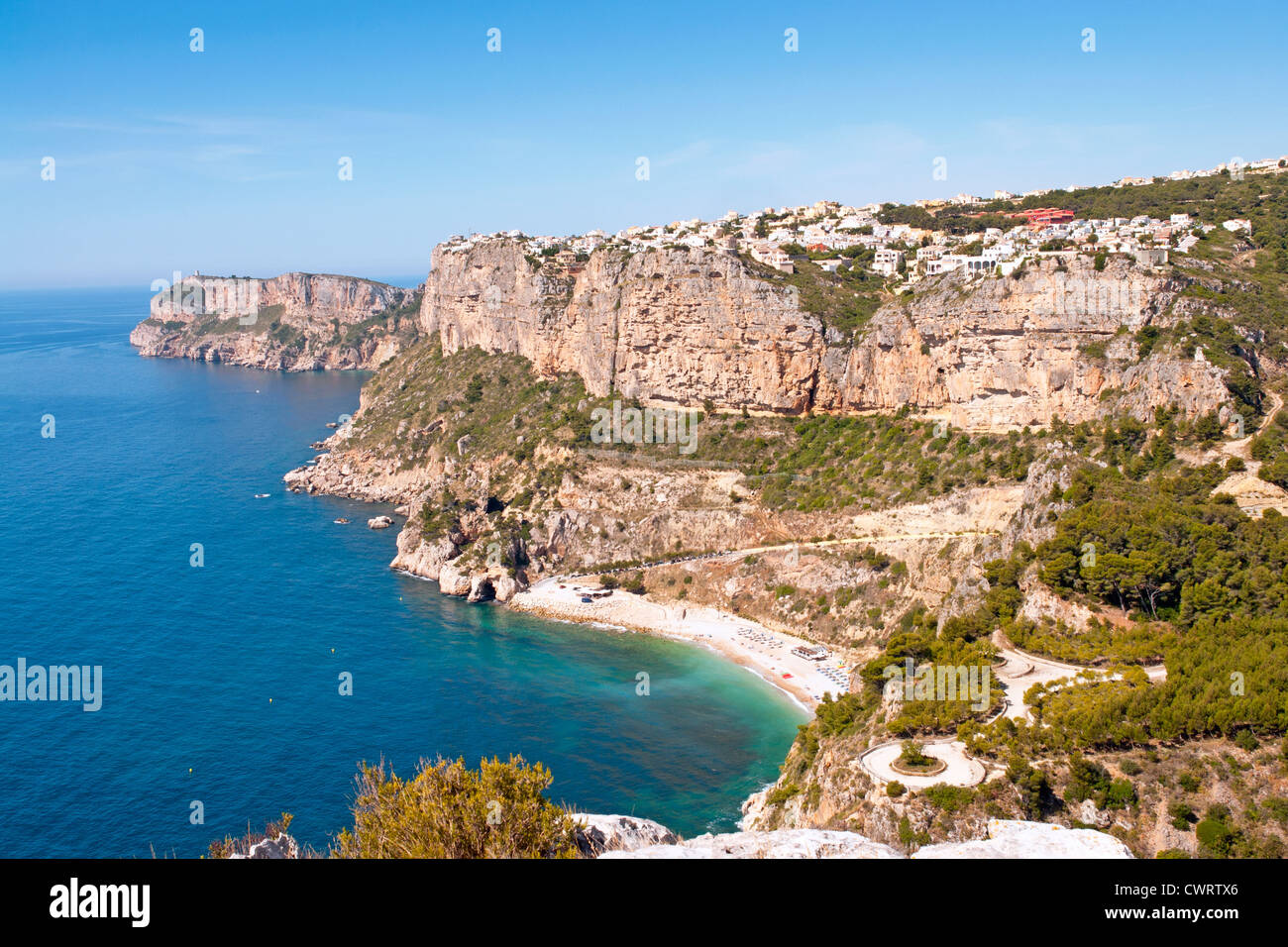 Cala del Moraig, with the urbanisation (urbanizacion) Cumbre del Sol. Benitachell on cliffs above,. Costa Blanca - Stock Image