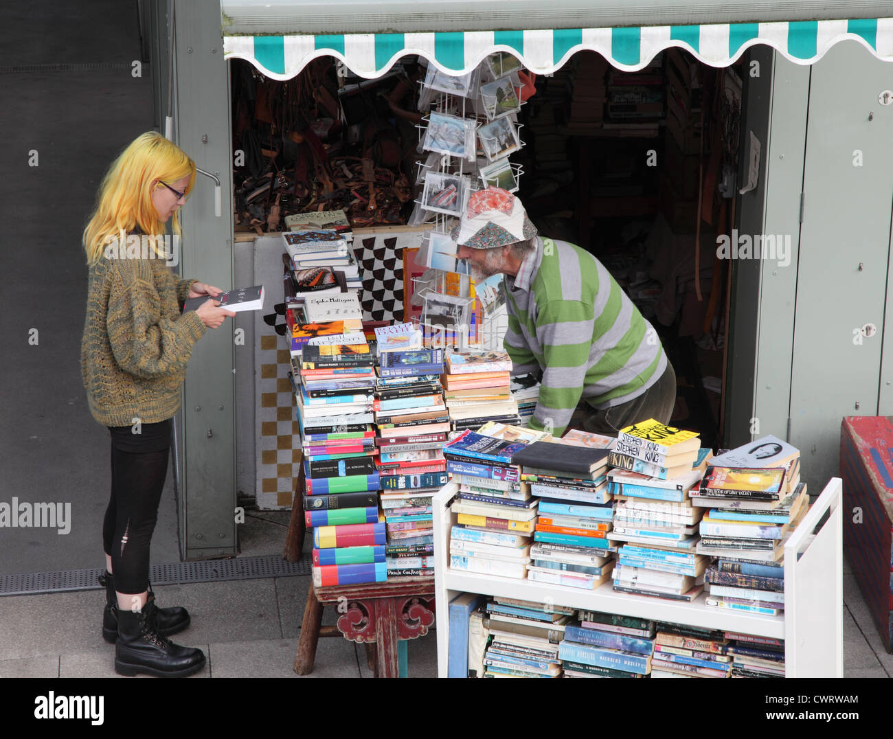 Male bookseller and female customer Norwich open air market East Anglia, England, UK - Stock Image