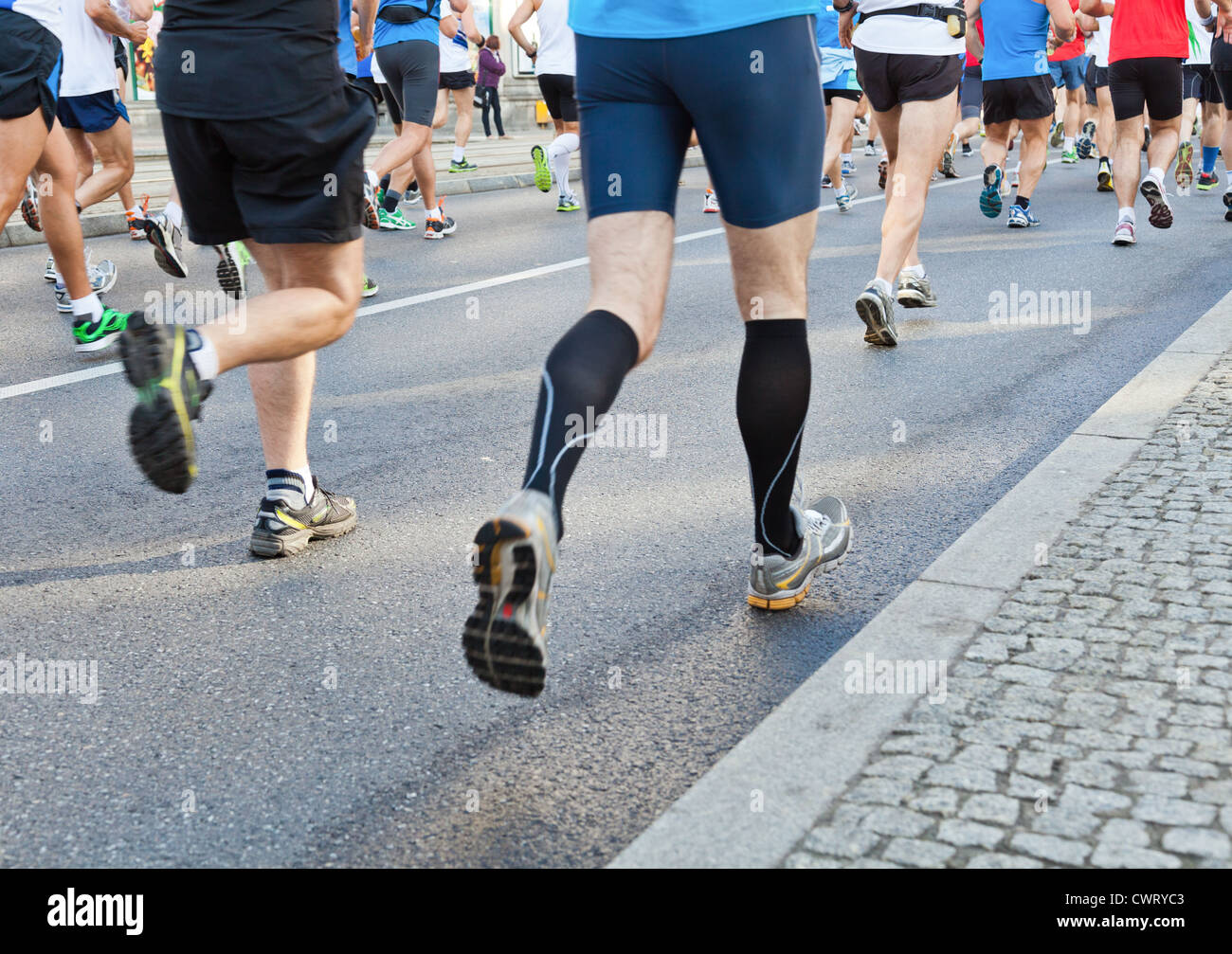 People running fast in a city marathon on street - Stock Image