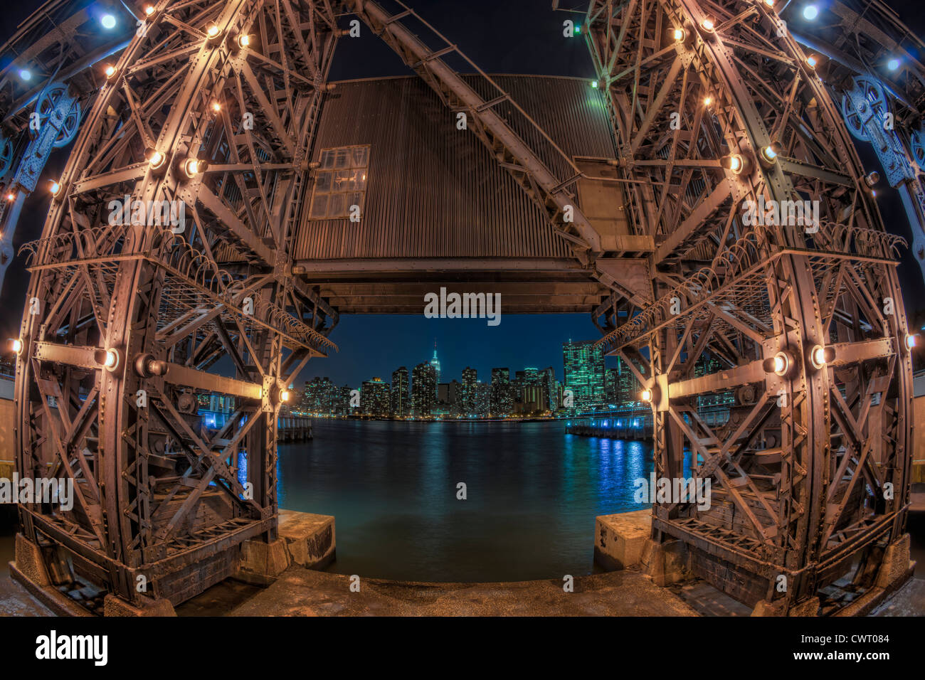The Manhattan night skyline framed by one of the gantry cranes across the East River in Gantry Plaza State Park. - Stock Image
