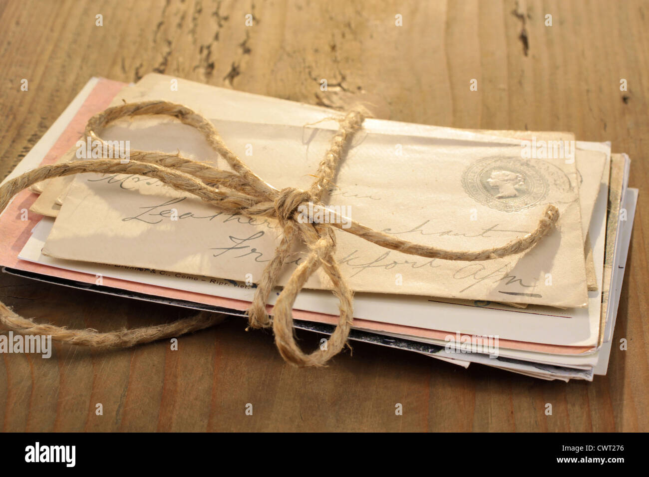 Bundle of letters tied with a cord on the old wooden table - Stock Image
