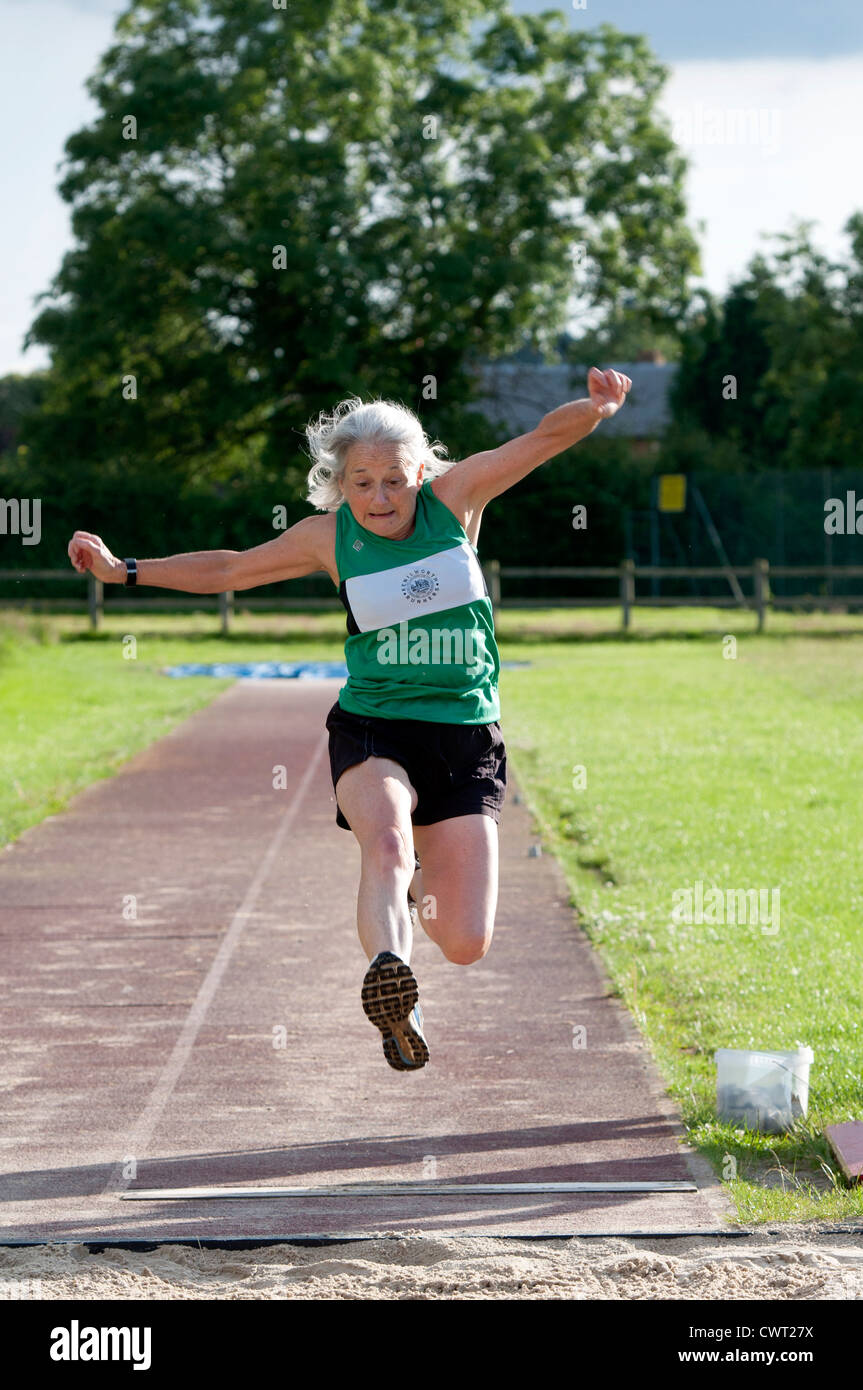 Elderly woman in long jump competition - Stock Image