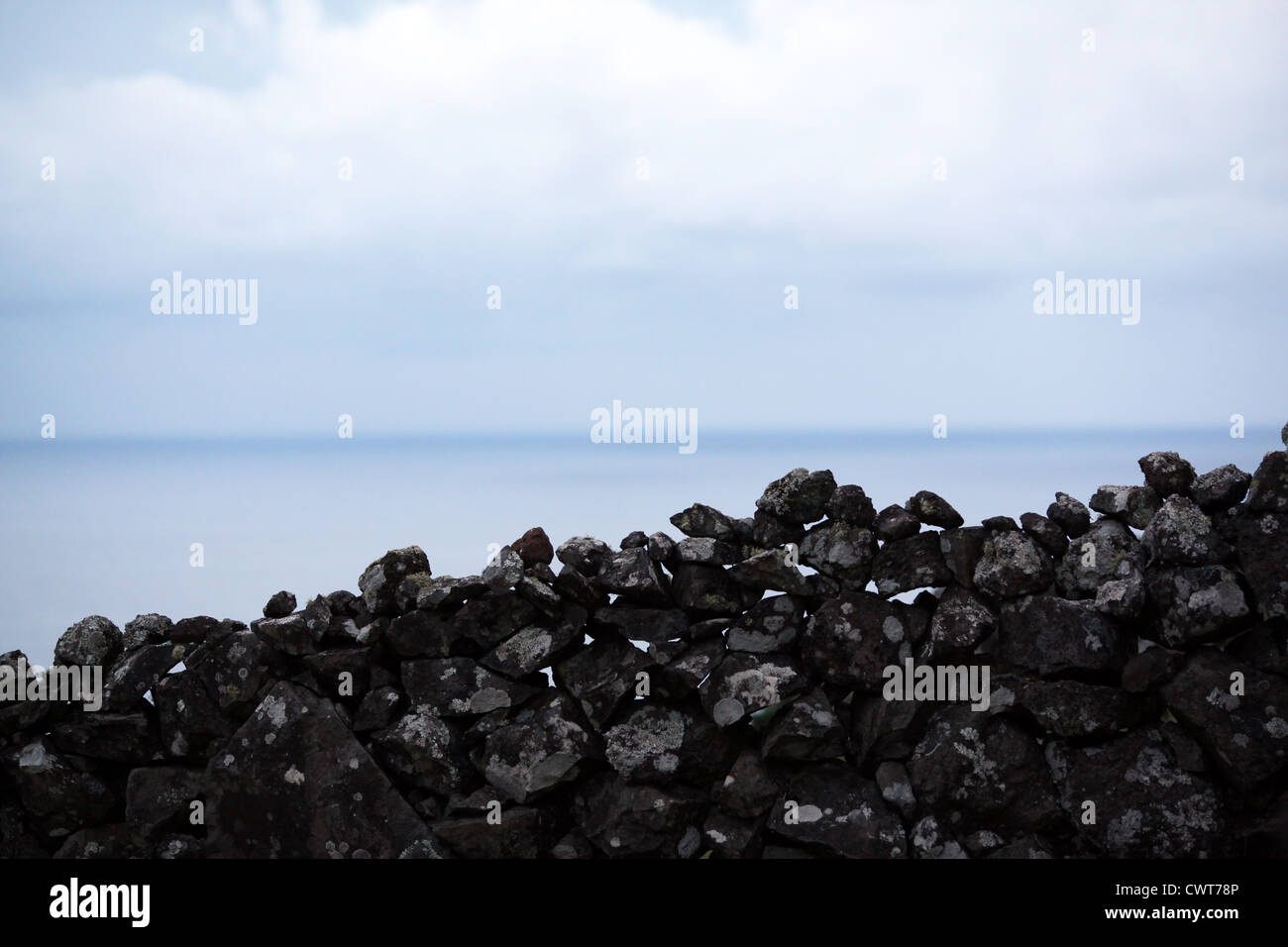 A typical azorean weathered wall separating agricultural terrains made of basalt rocks piled up on each other - Stock Image