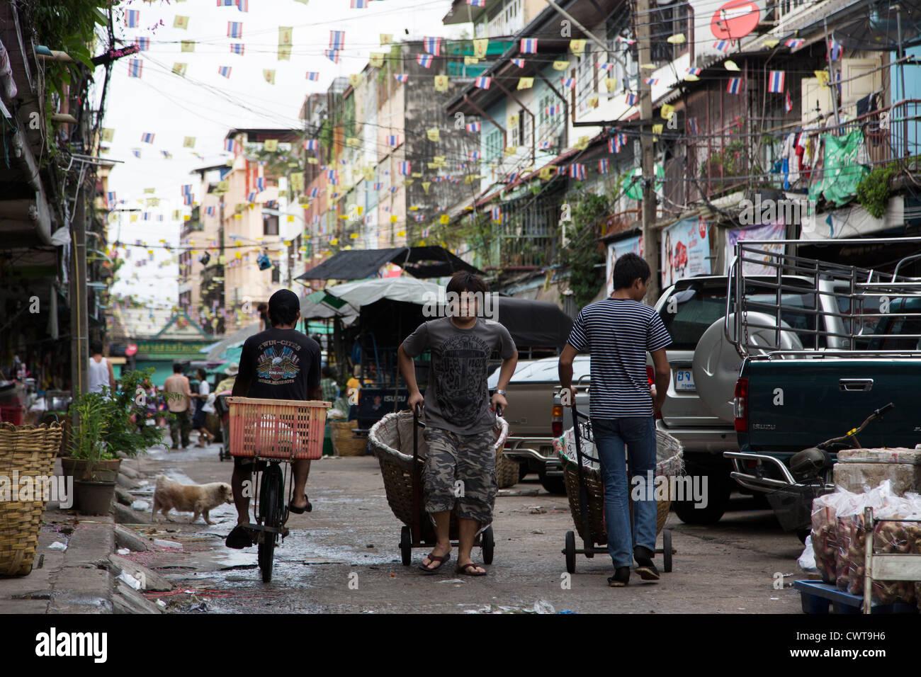 Thai worker pulling/pushing carts in the street around Pak Klong Talad (flower market) in Bangkok, Thailand Stock Photo