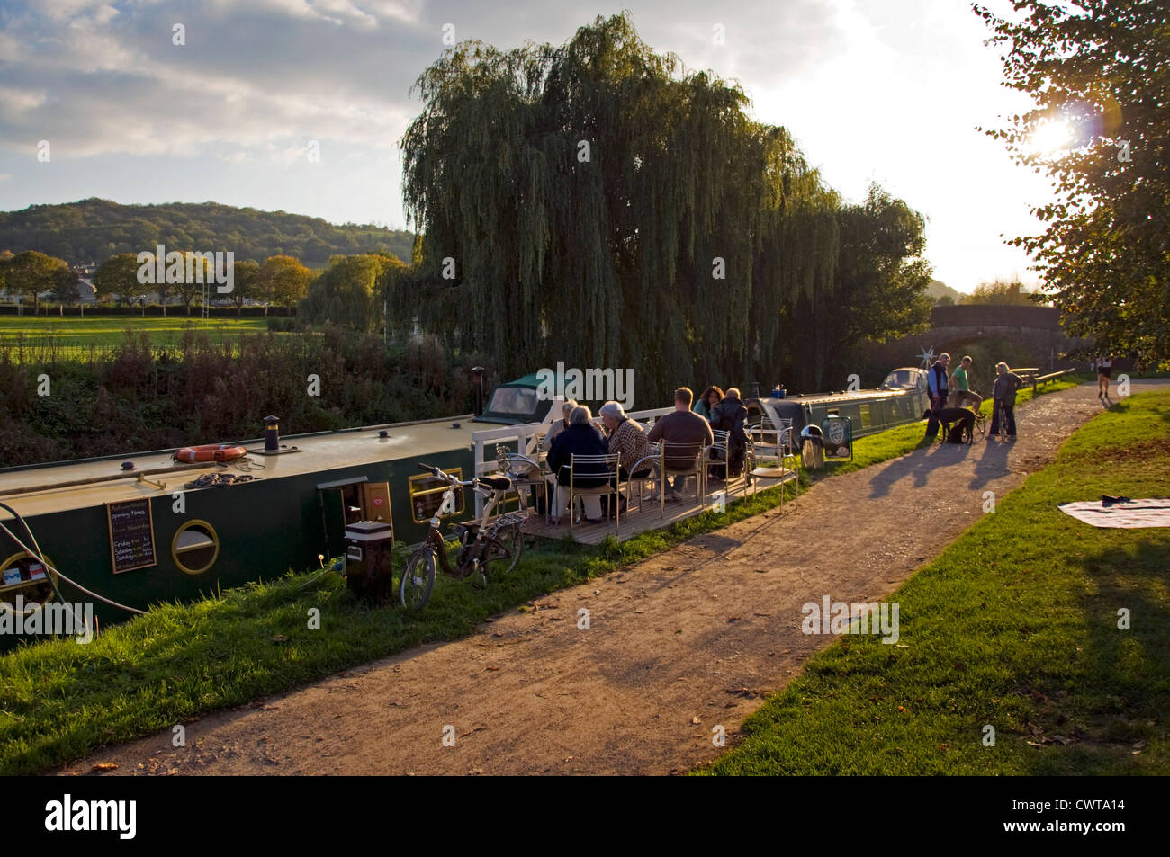 Customers sitting by the Kennet and Avon canal enjoying coffee tea and cakes at the Raft Cafe Boat - Stock Image