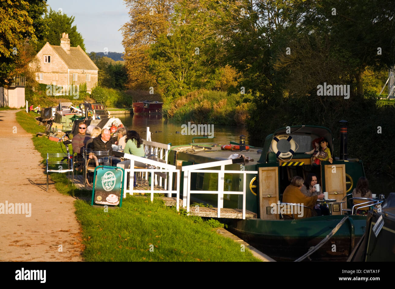 Customer sitting by the Kennet and Avon canal enjoying coffee tea and cakes at the Raft Cafe Boat - Stock Image