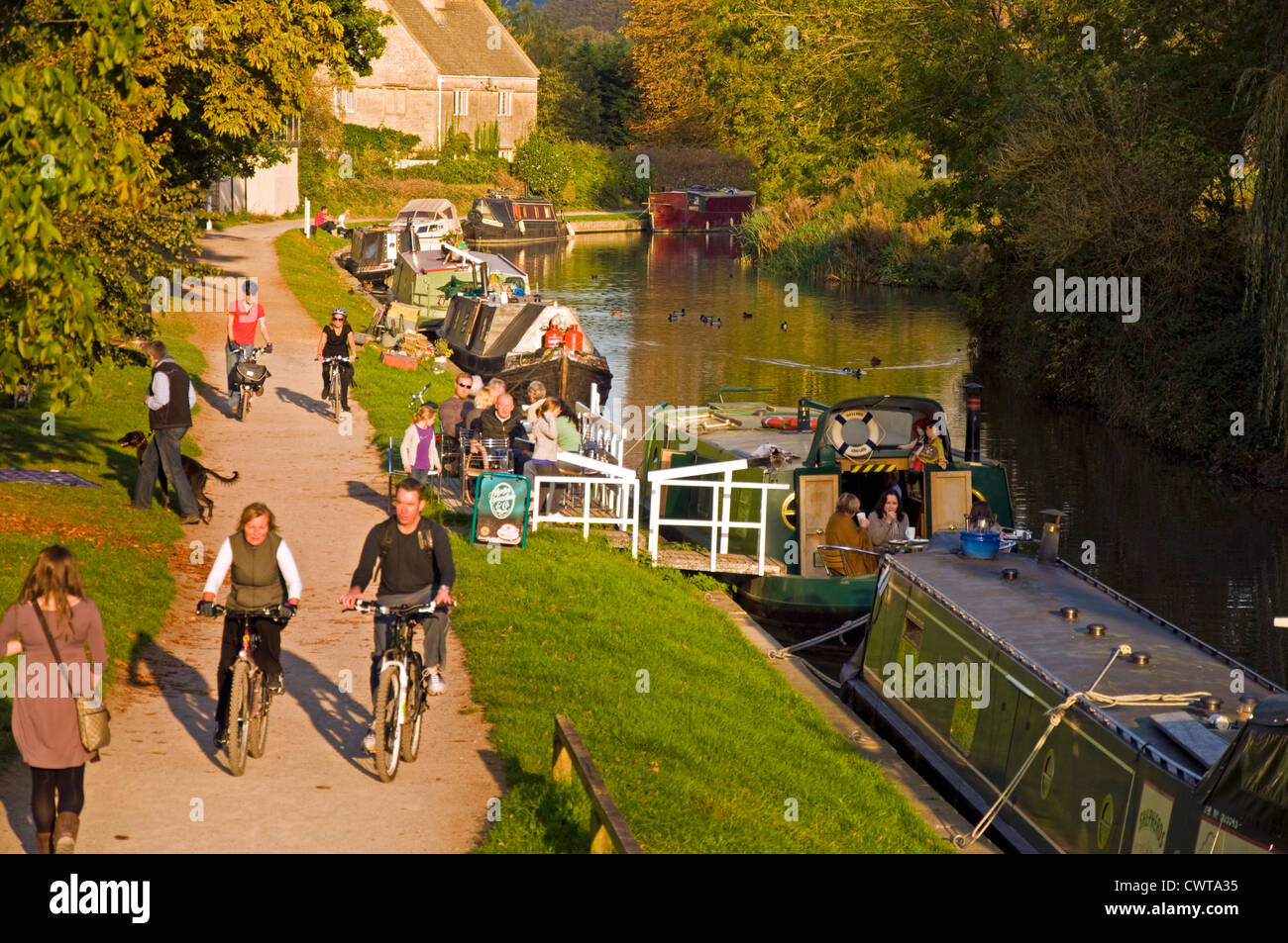 Customer sitting by the Kennet and Avon canal at the Raft Cafe Boat as people walk or cycle on the towpath - Stock Image