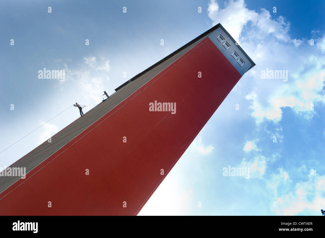 Person climbing at fade of a high-rise building - Stock Image