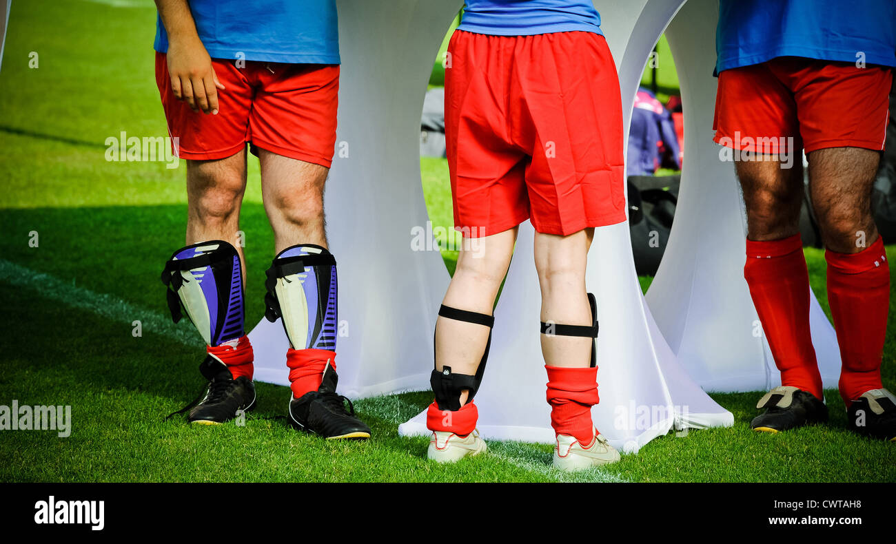 Three soccer players standing on soccer pitch - Stock Image