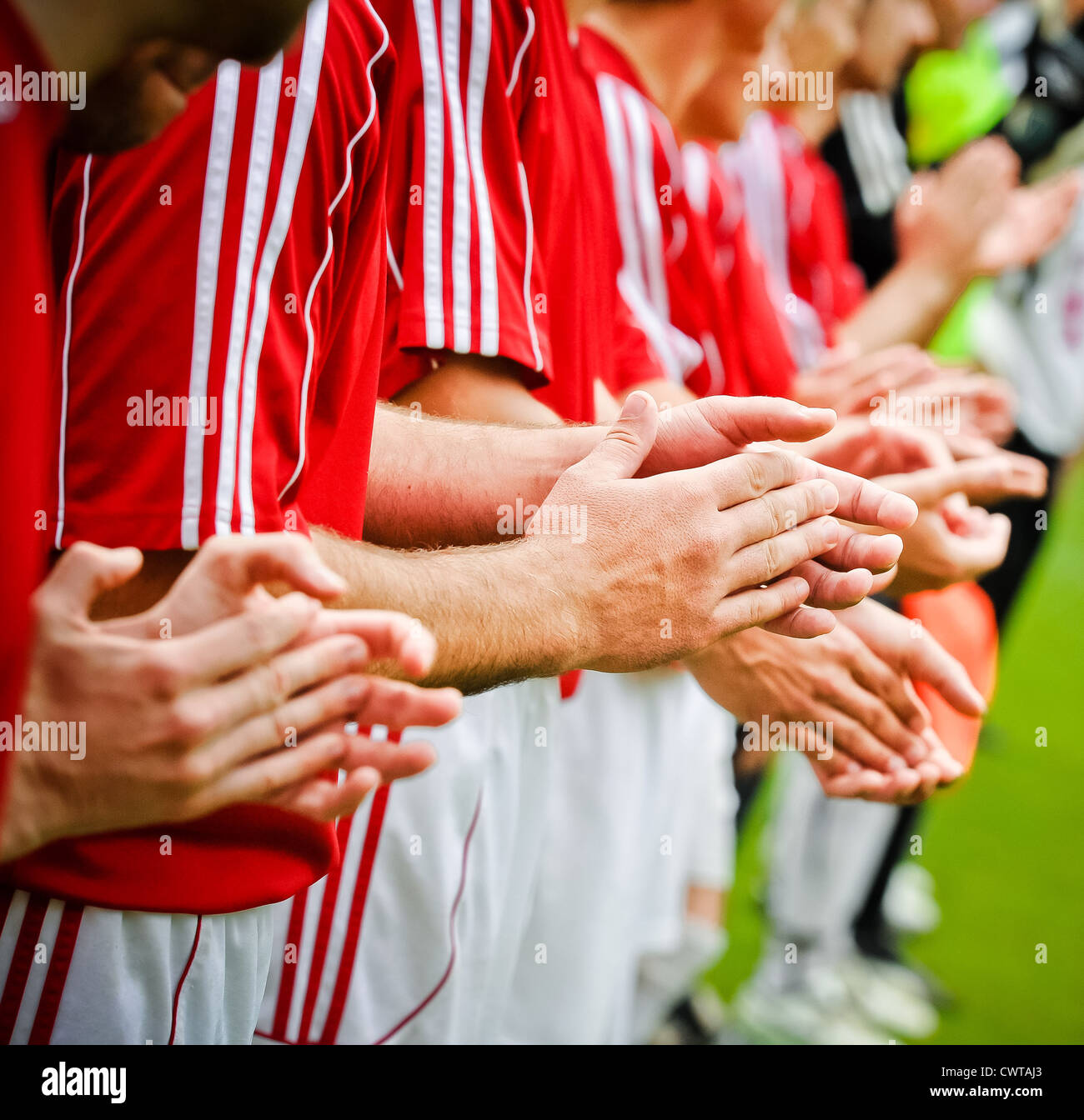 Three soccer players on soccer pitch applauding - Stock Image