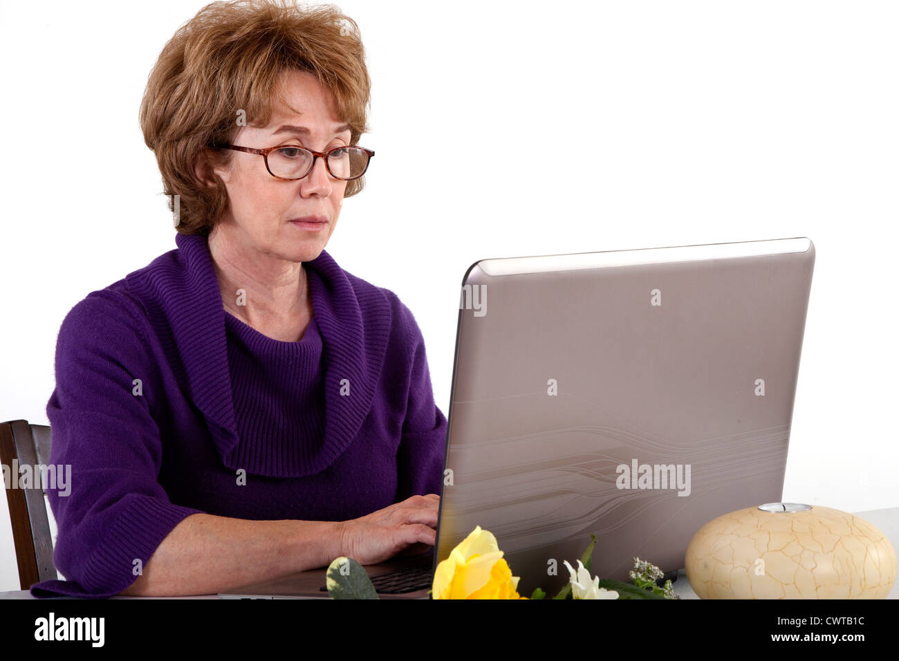 A mature woman who appears to be engrossed in whatever she sees on the screen of her laptop computer. Stock Photo