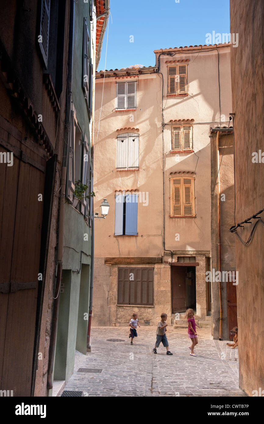 A street scene with young children running down a narrow cobbled street with tall houses on a sunny day in Provence, Stock Photo